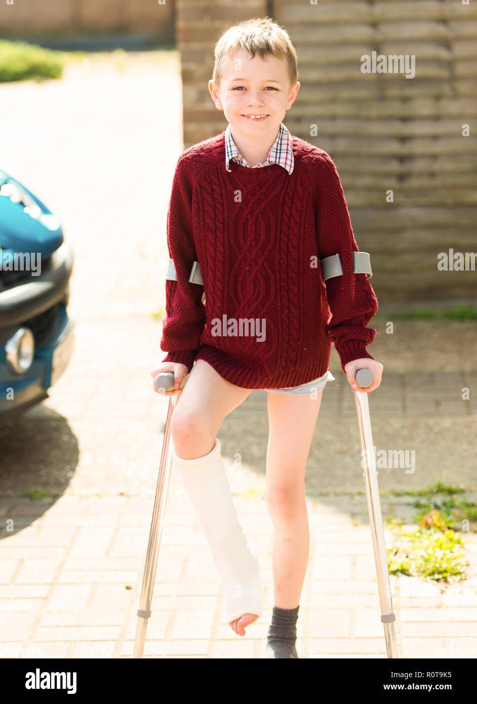 Einen kleinen Jungen mit ADHS, Autismus, Asperger Syndrom auf Krücken, nachdem er sein Bein gebrochen hat und dass Sie in einen Cast in Colchester General Hospital Stockfoto