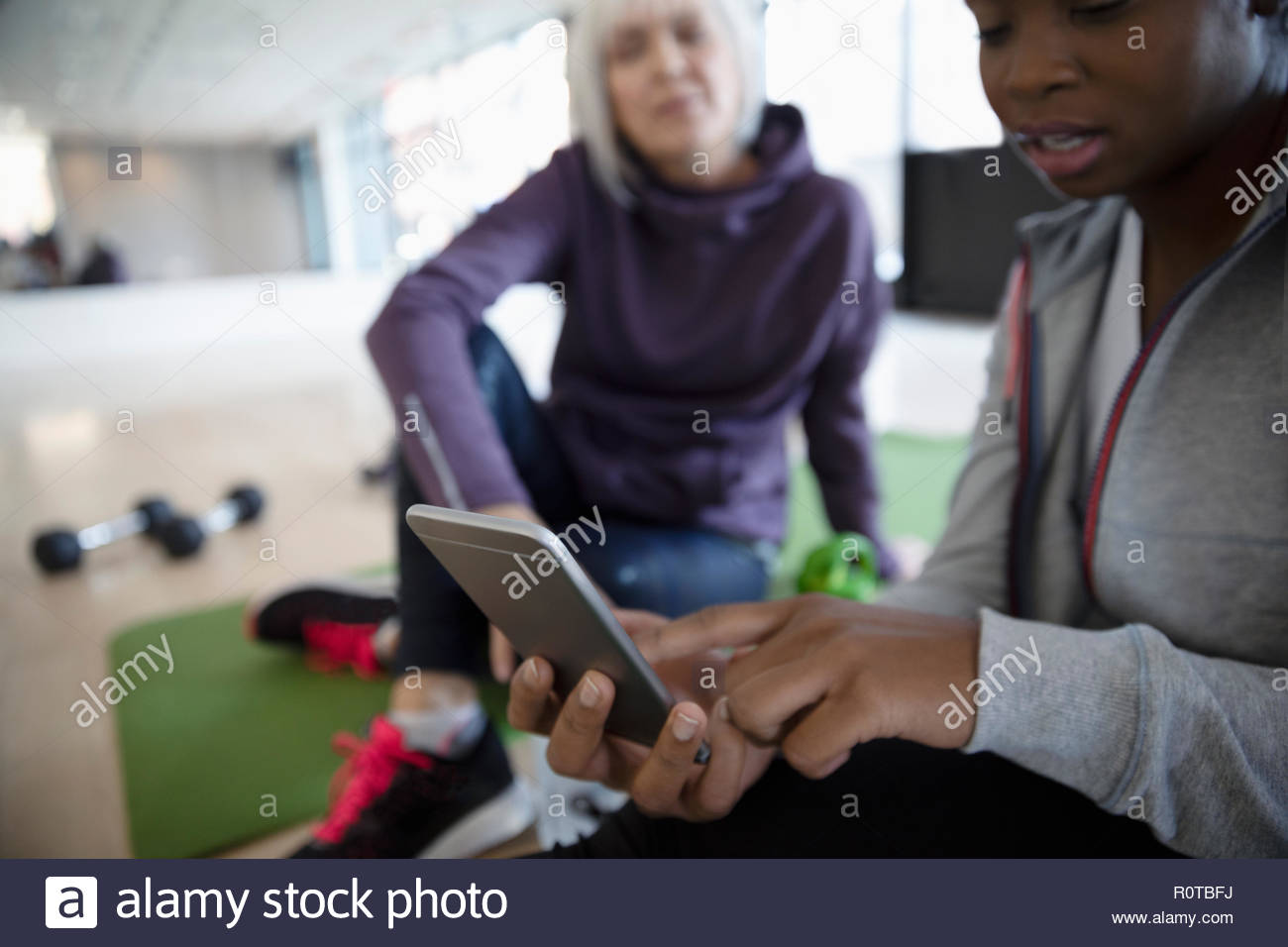 Frauen mit Smart Phone in der Turnhalle studio Stockbild
