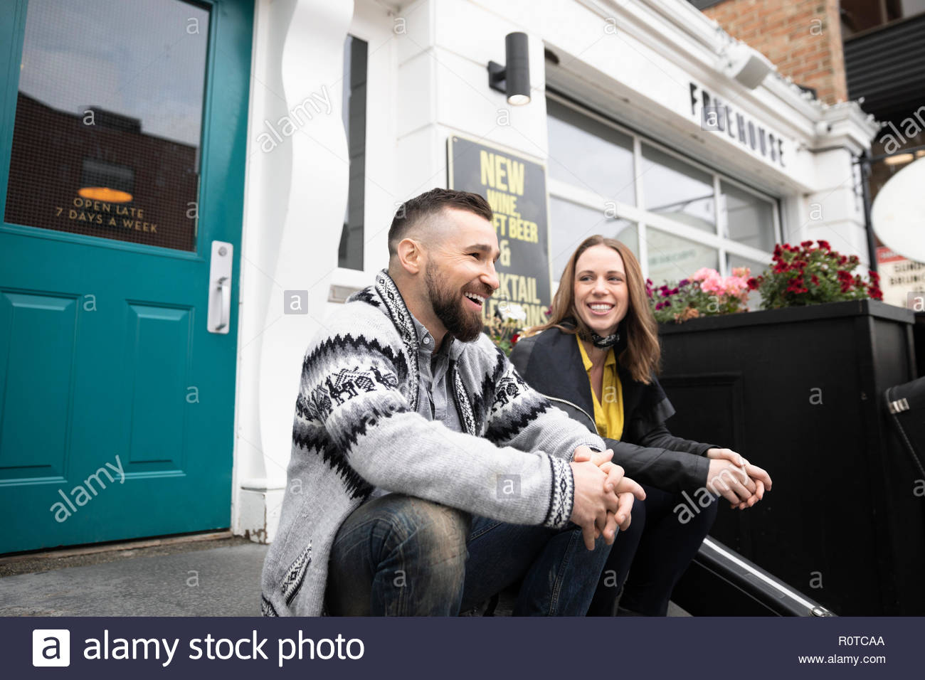Lächelnd Ehepaar miteinander reden außerhalb bar Stockbild