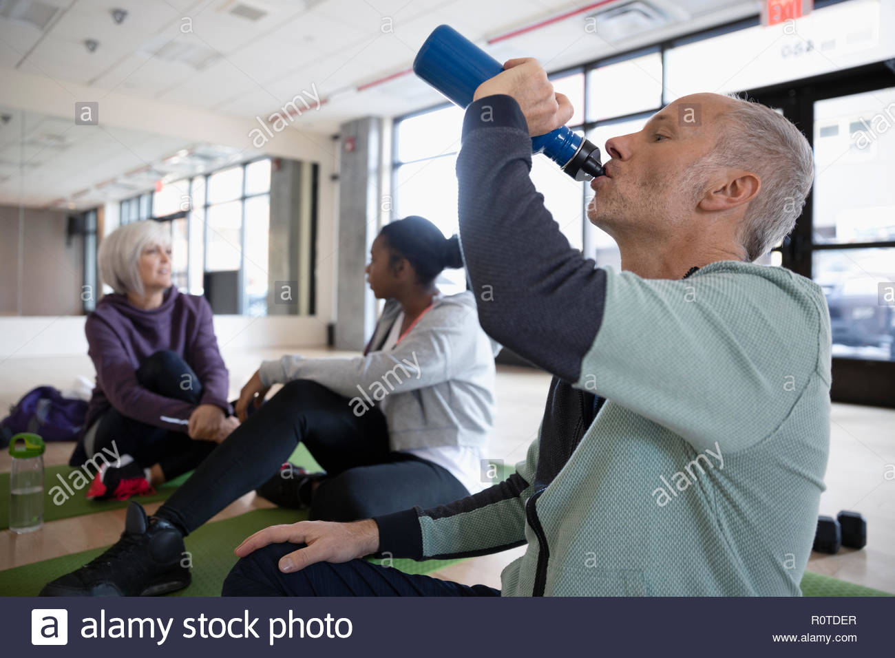 Man Trinkwasser in Fitness Studio Stockbild