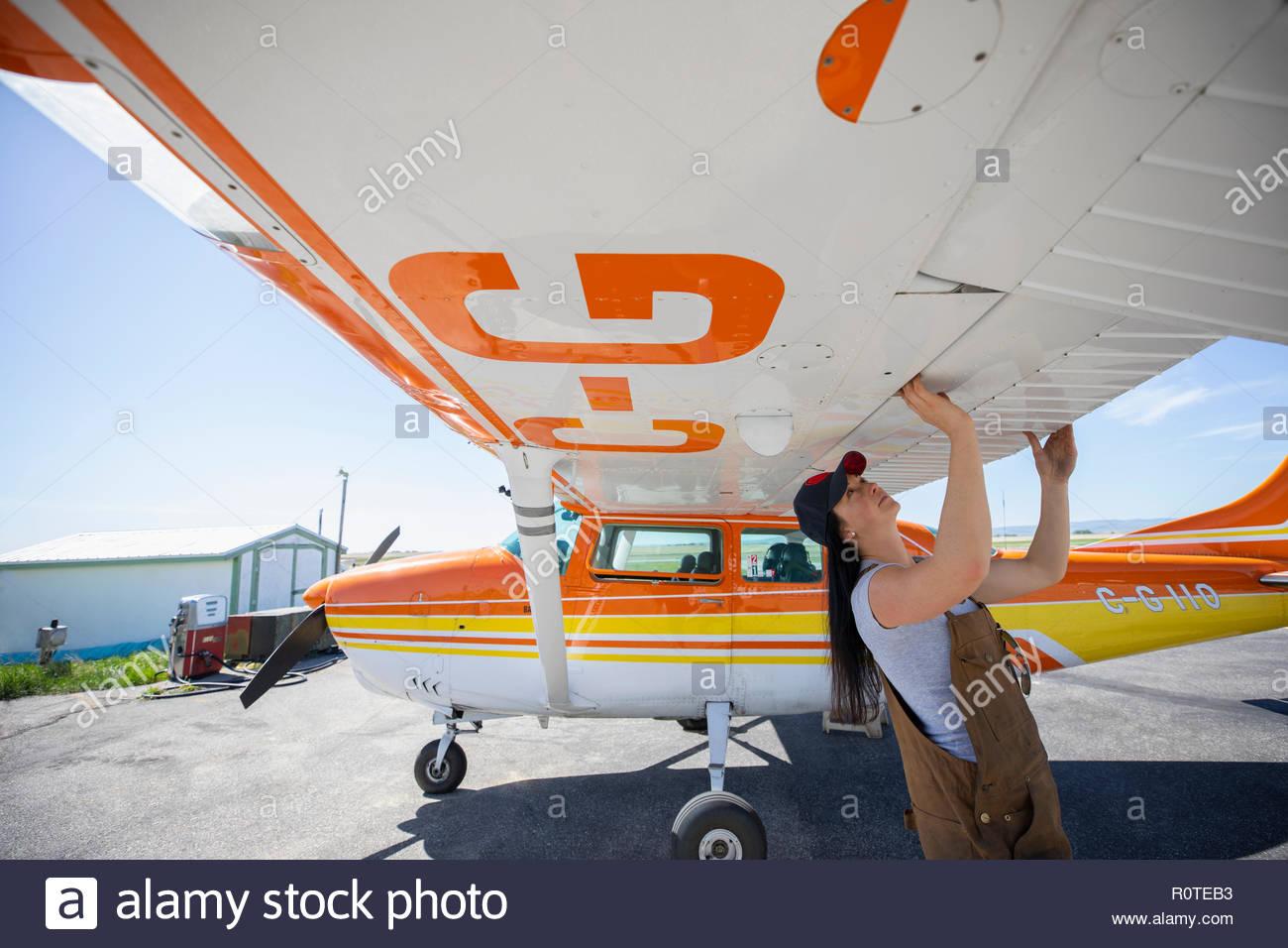 Ingenieurin Kontrolle Flügel des Flügelrads Flugzeug auf Asphalt Stockbild