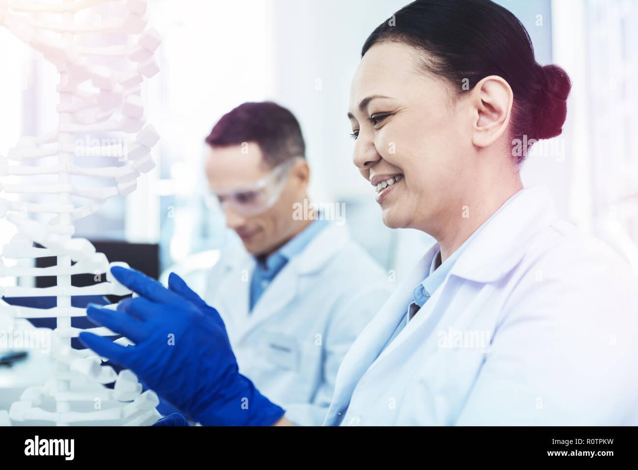 Heiter erfreut, Frau an der DNA-Modell suchen Stockbild