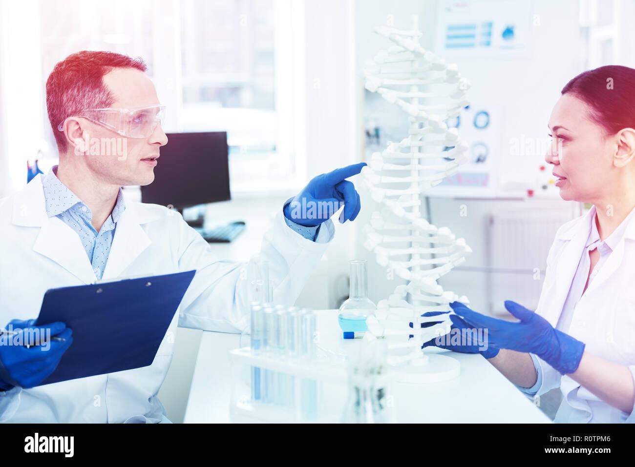 Ernsthafte junge Mann an der DNA-Modell zeigen Stockbild