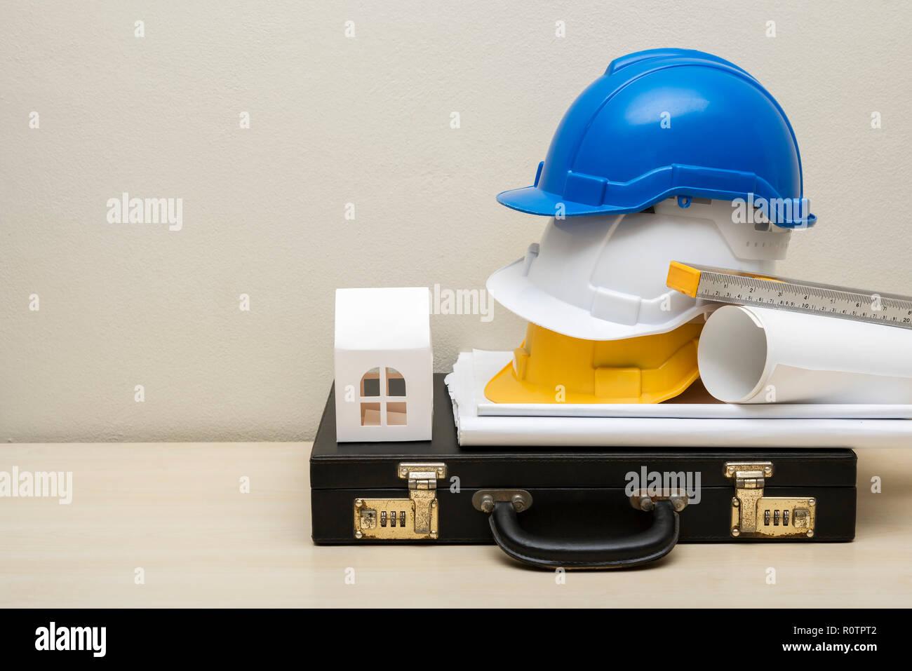 Engineering Zubehör, Helme, Haus Papier Modell, Business Tasche, Blaupause, auf Holz Tisch mit weißer Beton Wand Hintergrund. Bild zum Text hinzufügen Stockbild