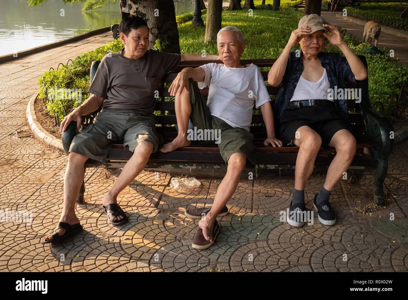Männer im mittleren Alter sprechen auf einer Parkbank durch Hoan Kim See, Hanoi, Vietnam. Stockfoto