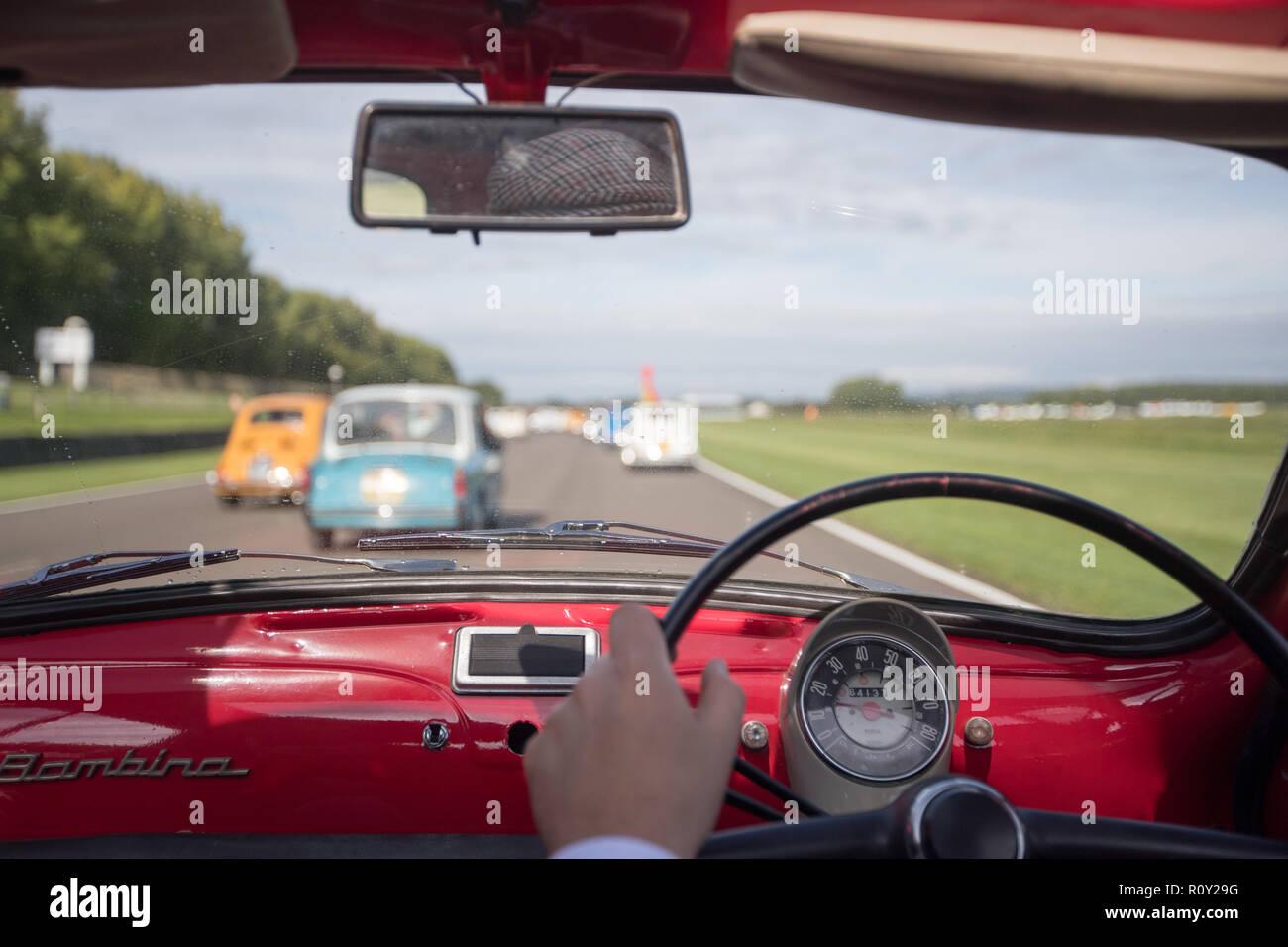 Im Inneren des kleinen italienischen Fiat 500 Auto zwar um eine Runde fahren in Goodwood Rennstrecke genommen. Stockbild