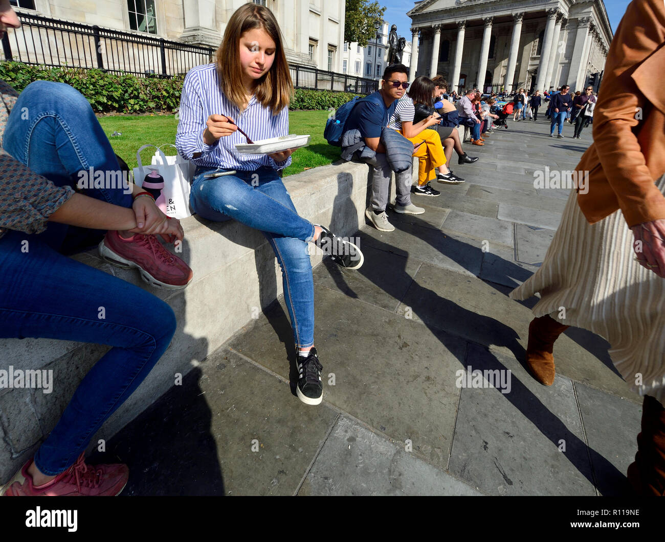 Menschen entspannend am Mittag vor der National Gallery am Trafalgar Square, London, England, UK. Stockbild