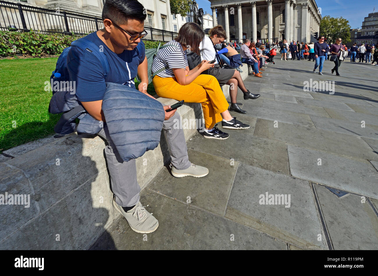 Menschen auf ihren Handys am Mittag vor der National Gallery am Trafalgar Square, London, England, UK. Stockbild