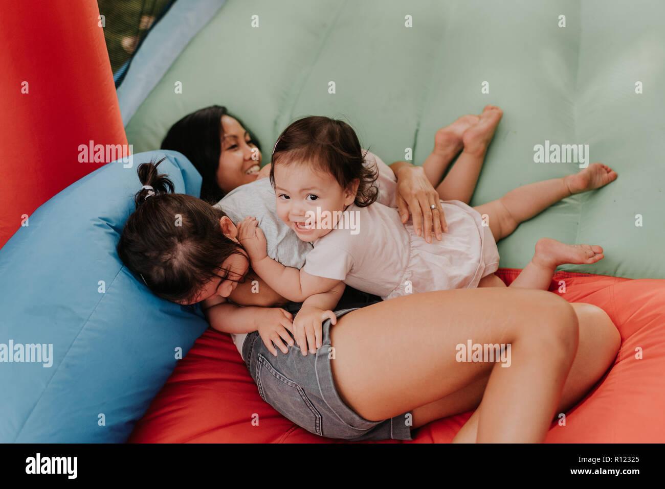 Mutter und Töchter spielen auf Hüpfburg Stockbild
