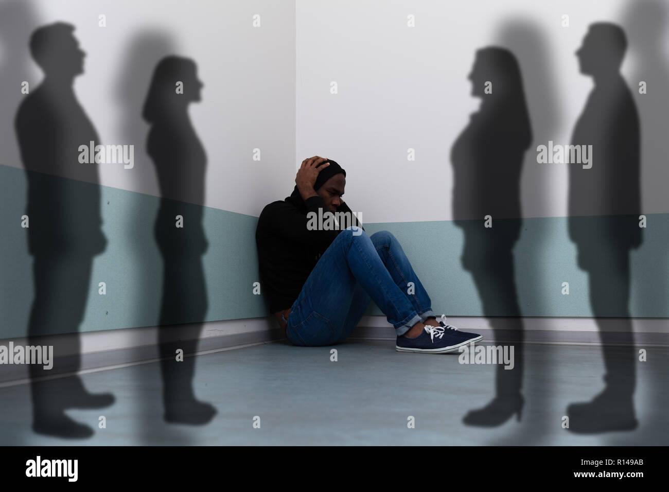 Die Schatten von Menschen, die in der Nähe von Angst Mann sitzt auf dem Boden Stockbild