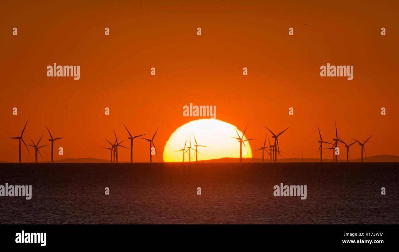 Sonnenuntergang über dem Meer mit Windkraftanlagen am Horizont Stockbild