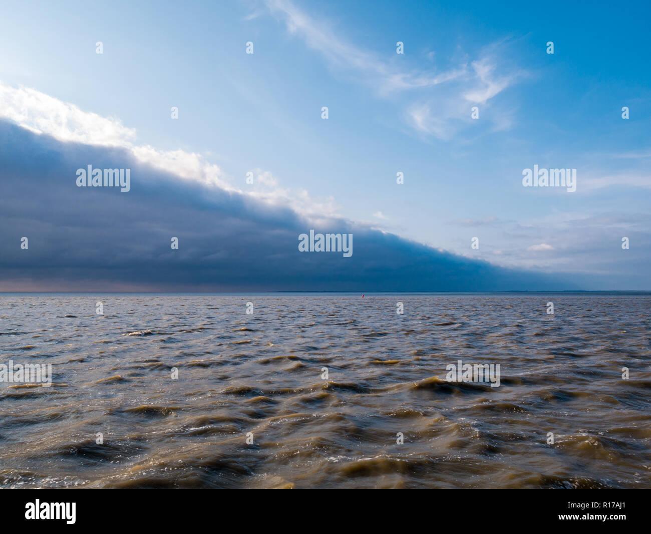 Vorderkante mit Linie der Sturmwolken des kalten Wetters vorne nähert sich blauer Himmel auf rauen Wasser des Wattenmeer, Niederlande Stockbild