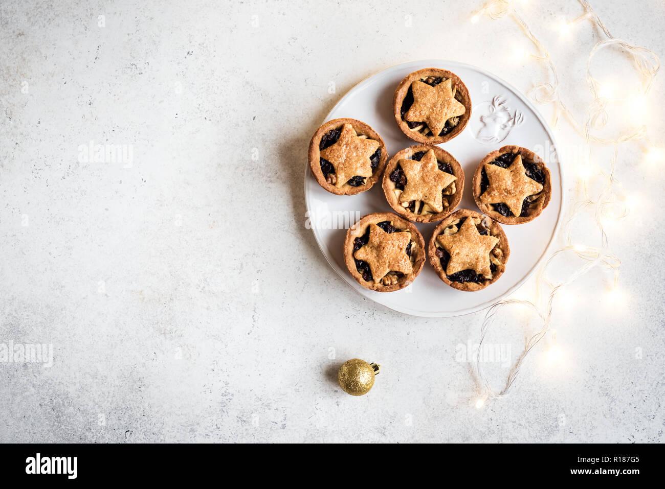 Mince Pies für Weihnachten auf weißem Hintergrund mit Licht, kopieren. Traditionelle Weihnachten Dessert - Kuchen mit Früchten und Nüssen vor den Mund. Stockfoto