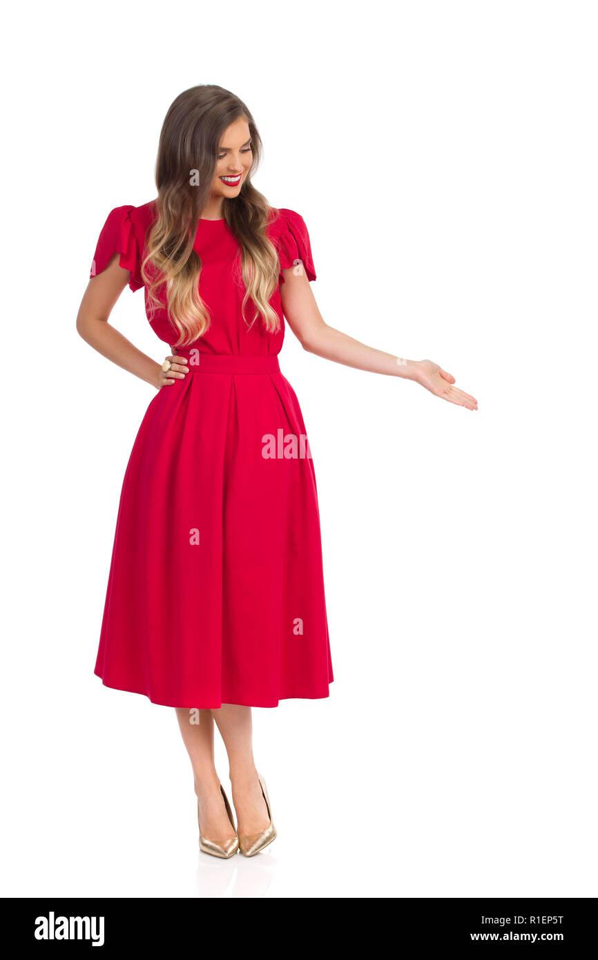 0337cb6e03b5c Schöne junge Frau im roten Kleid und gold High Heels ist weg schauen ...