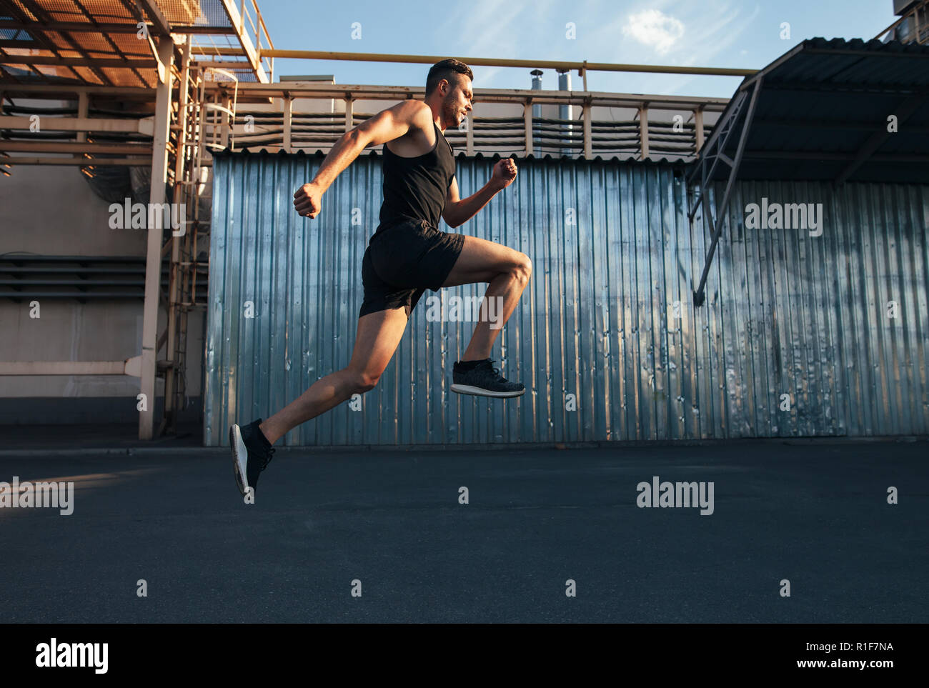 Hübscher junger Mann in ndustrial Gebäude Hintergrund. Läufer, Jogger, Fitness Stockbild