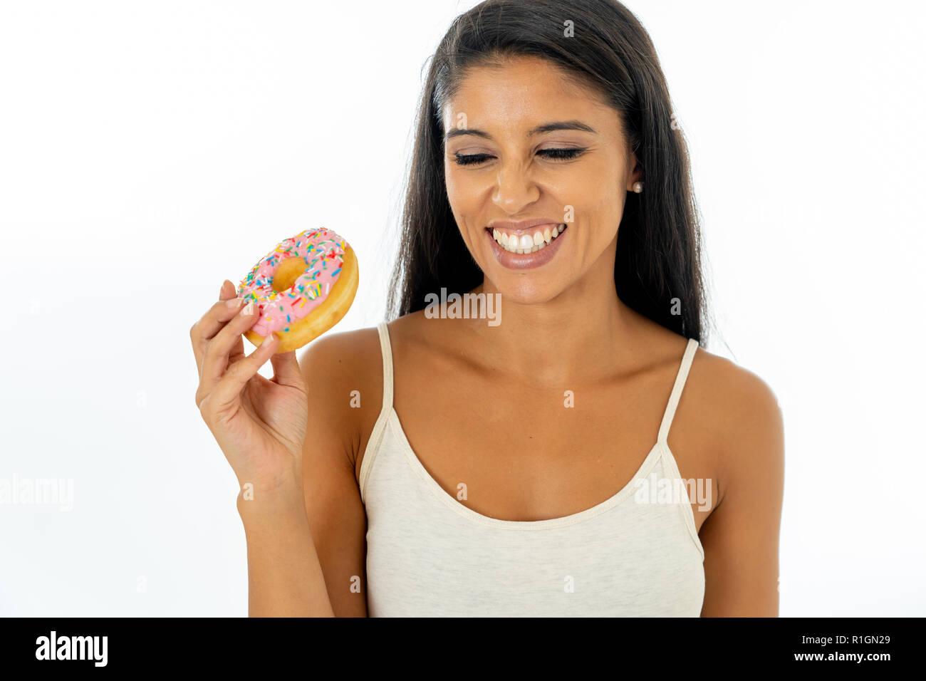 Portrait von extrem glücklich Schöne lateinische junge Frau essen eine leckere Doughnuts es mit Freude in sich selbst verwöhnen und vergessen di Stockbild