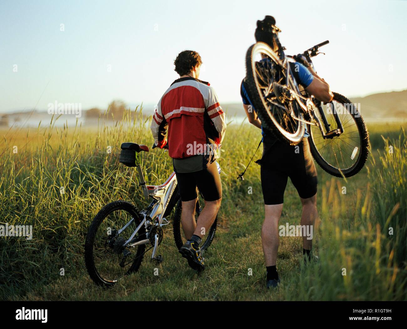 Zwei männliche Wandern ihre Fahrräder entlang einer Spur. Stockfoto