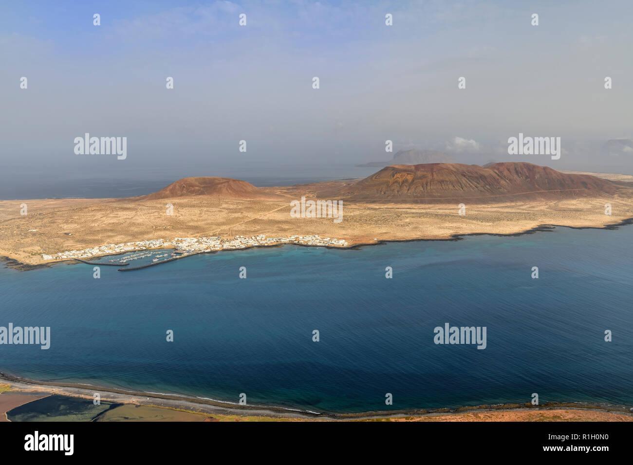Die kleinen Fischen und touristischen Dorf Caleta del Sebo auf der winzigen Insel La Graciosa neben Lanzarote Kanarischen Inseln. Mount Bermeja ist hinter einer Stockbild