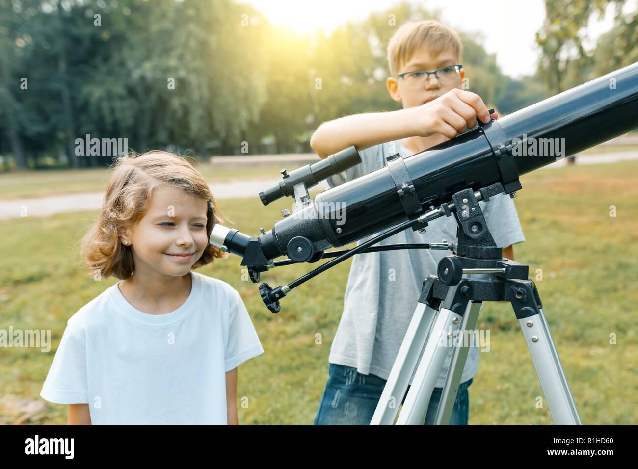 Kinder schauen mit interesse an einem teleskop in den himmel