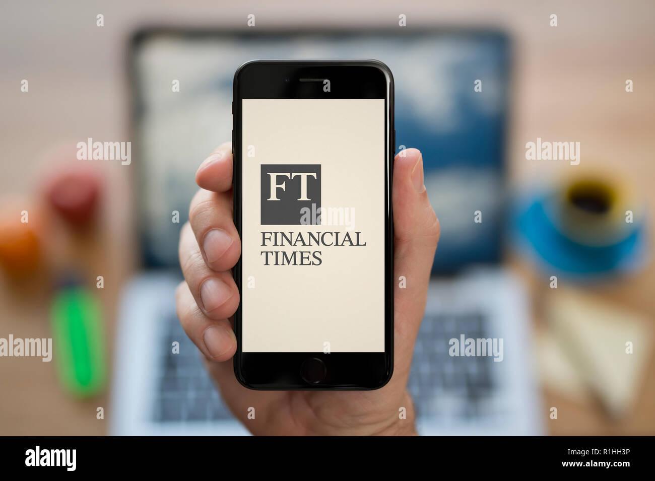 Ein Mann schaut auf seinem iPhone zeigt die Financial Times logo, während saß an seinem Computer Schreibtisch (nur redaktionelle Nutzung). Stockbild