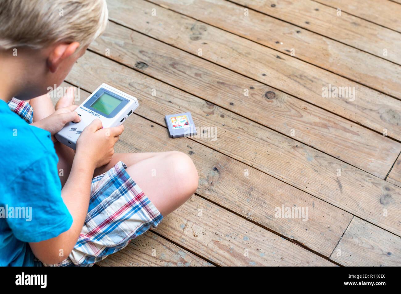 Junge mit seinem Nintendo Gameboy Computerspiele zu spielen. 90er Jahre Ambiente. im Innenbereich. Stockbild