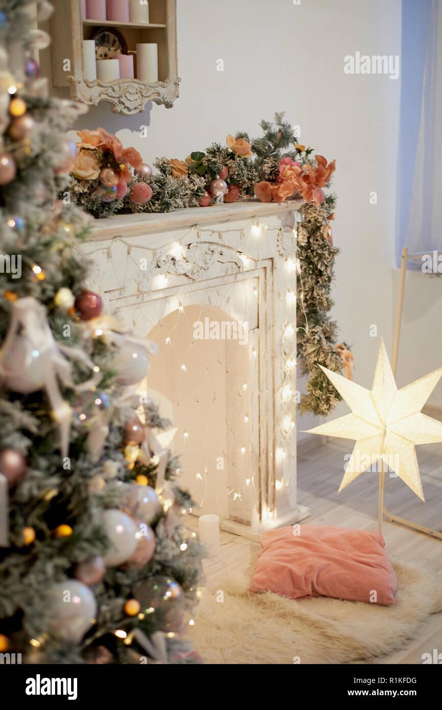 Gemütliche helle Interieur im neuen Jahr Stil. Dekorativer Kamin, Lichter, Weihnachtsbaum mit Geschenken. Neues Jahr Feier und Vorbereitung. Stockfoto