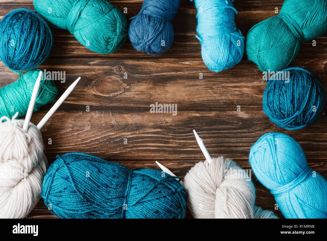Flach mit arrangiert Garn clews und Stricknadeln auf Holz- Oberfläche Stockfoto