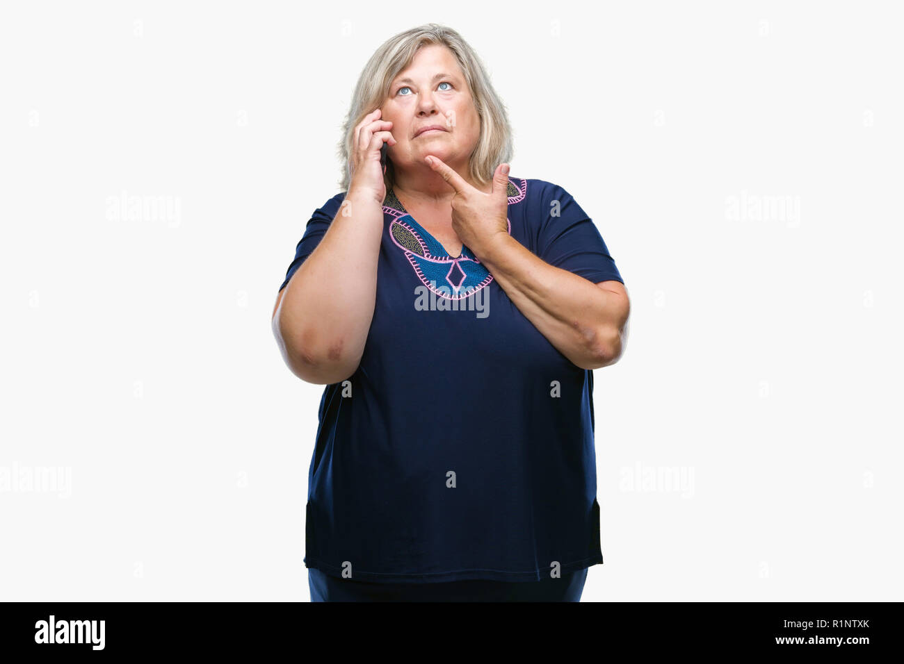 Senior Plus size kaukasische Frau am Telefon zu sprechen über isolierte Hintergrund ernstes Gesicht denken über Frage, sehr verworrene Vorstellung Stockfoto