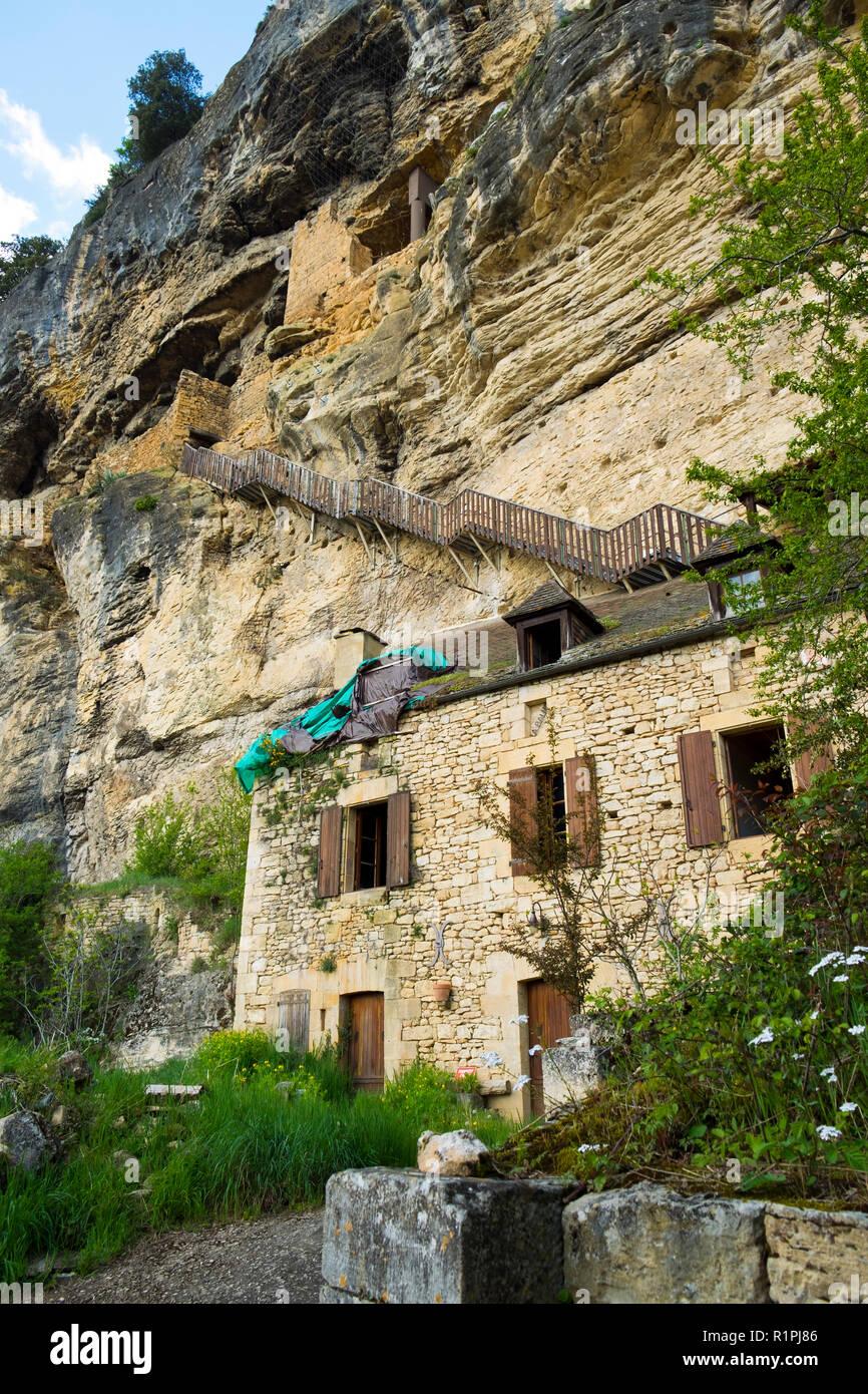 La Roque-Gageac, Frankreich - 3 April 2017: Verlassene Häuser unter den Klippen in La Roque-Gageac in der Dordogne, Nouvelle Aquitaine, Frankreich. Stockbild