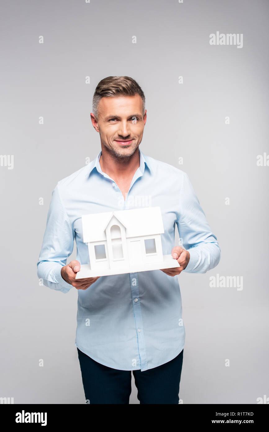 Lächelnd erwachsenen Mann hält Papier Modell von Haus isoliert auf weiss Stockbild