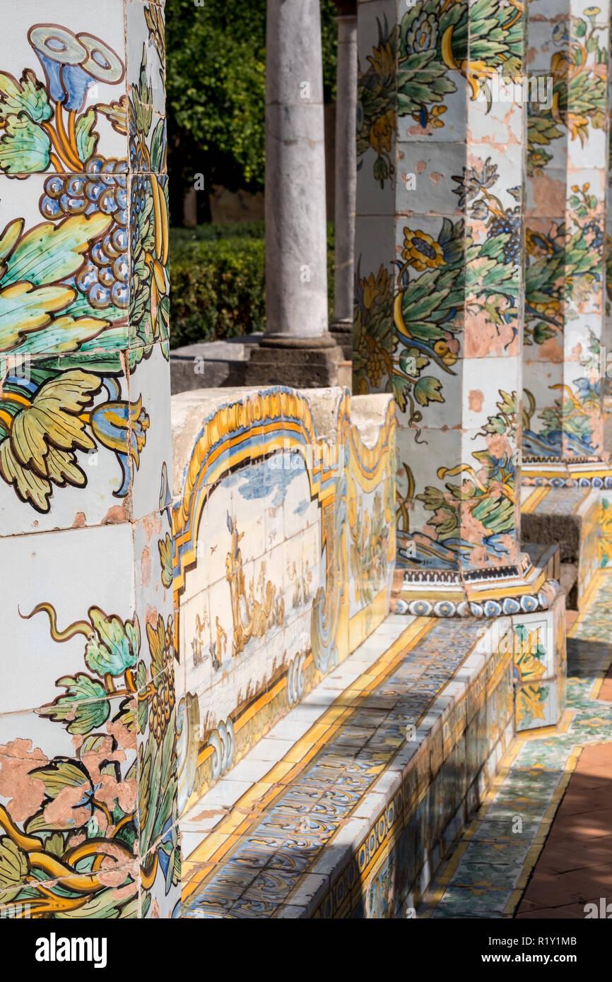 Bunte Fliesen- Säulen und Sitzbank im Garten des Kreuzgangs im Santa Chiara Kloster in der Via Santa Chiara, Neapel Italien. Stockbild