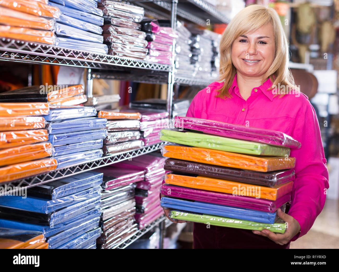 Portrait von reife Frau zeigt Stapel Bettlaken in der Textil shop Stockfoto