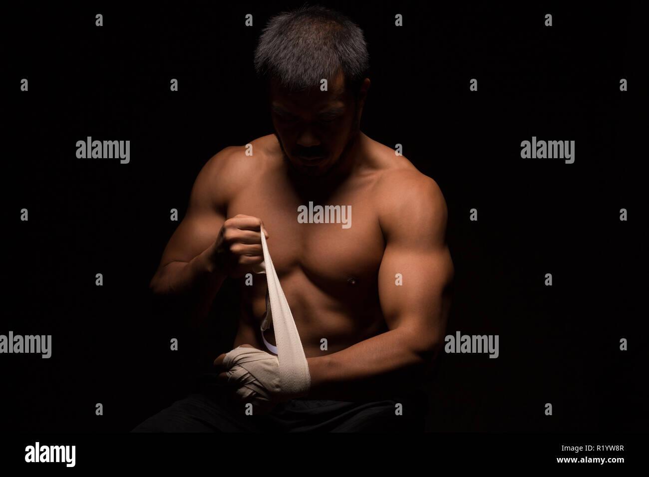 Asiatischer Mann mit muskulösen Oberkörper ist die Vorbereitung für den Kampf Stockbild