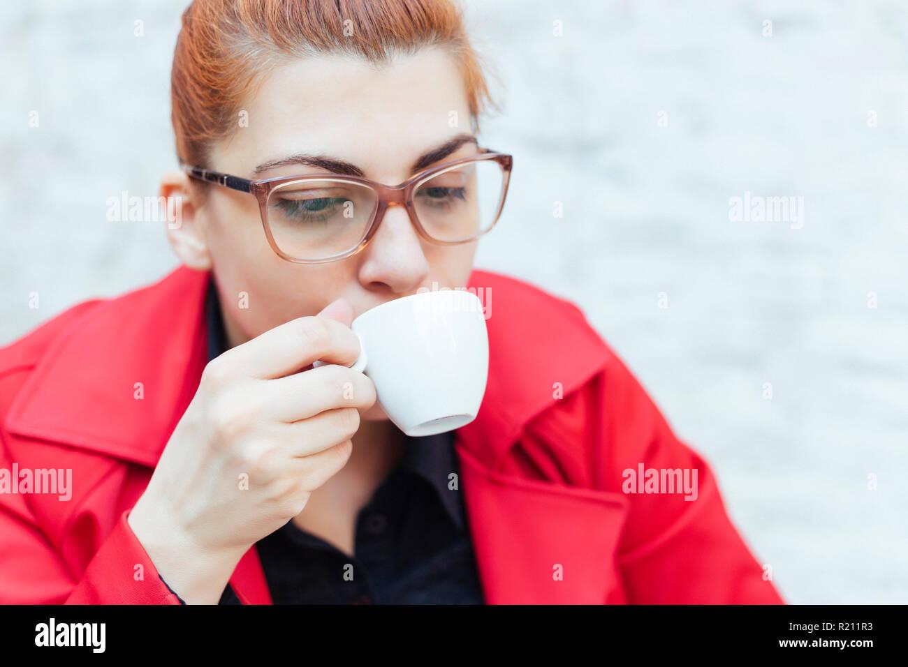 redhead grild in einem roten mantel trinken einen espresso stockfoto