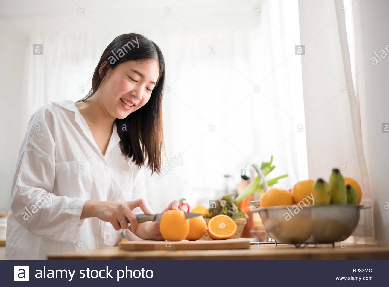 Zugeschnittenes Bild der alten Frau schneiden Obst in der Küche. Gesundes Essen. Obstsalat Vorbereitung Stockbild