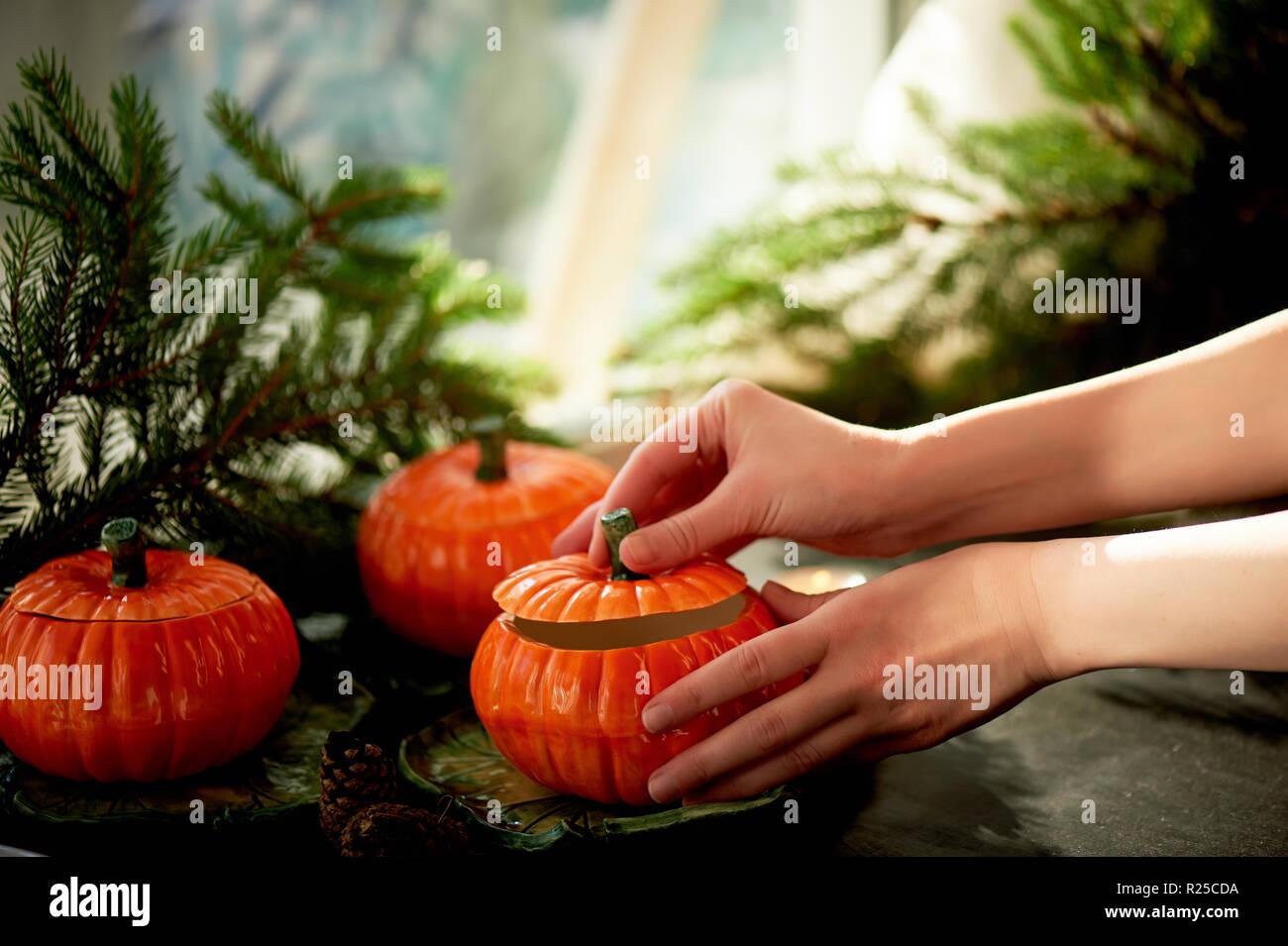 Handgefertigte Keramik in Form von kürbisse. Weihnachten Pfoten. Die Atmosphäre der Feier und Wohnkomfort. Hände öffnen Sie den Deckel auf den Topf. Stockbild