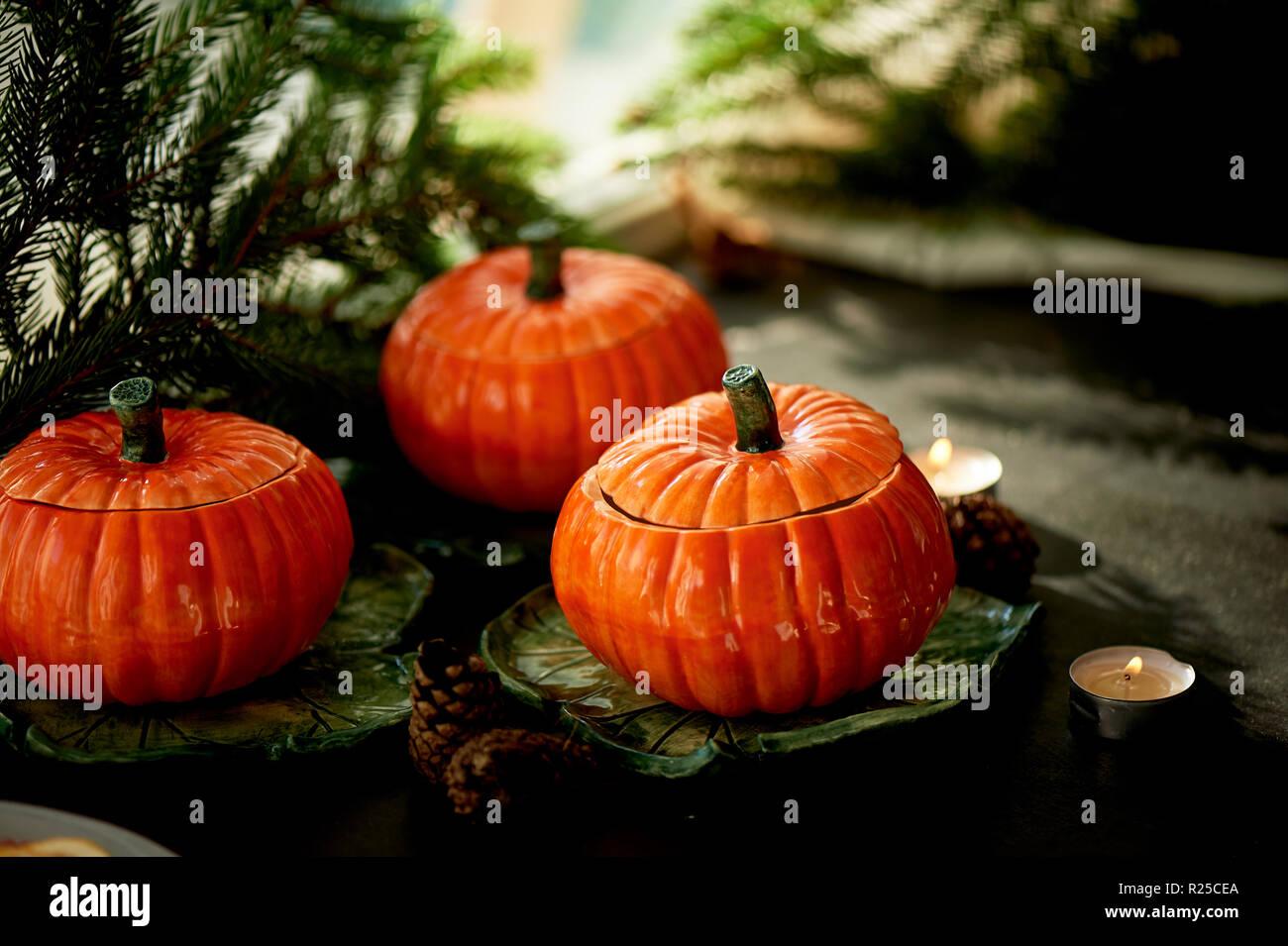 Handgefertigte Keramik in Form von kürbisse. Weihnachten Pfoten. Die Atmosphäre der Feier und Wohnkomfort. Fröhliches orange Töpfe auf dem Herd und Braten. Stockbild