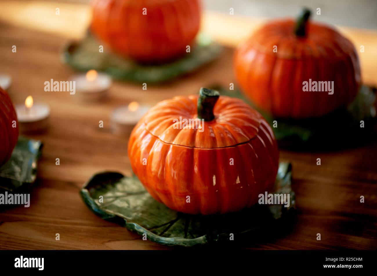 Handgefertigte Keramik in Form von Kürbissen. Die Atmosphäre der Feier und Wohnkomfort. Fröhliches orange Töpfe auf dem Herd und Braten. Kürbis Brei Stockbild
