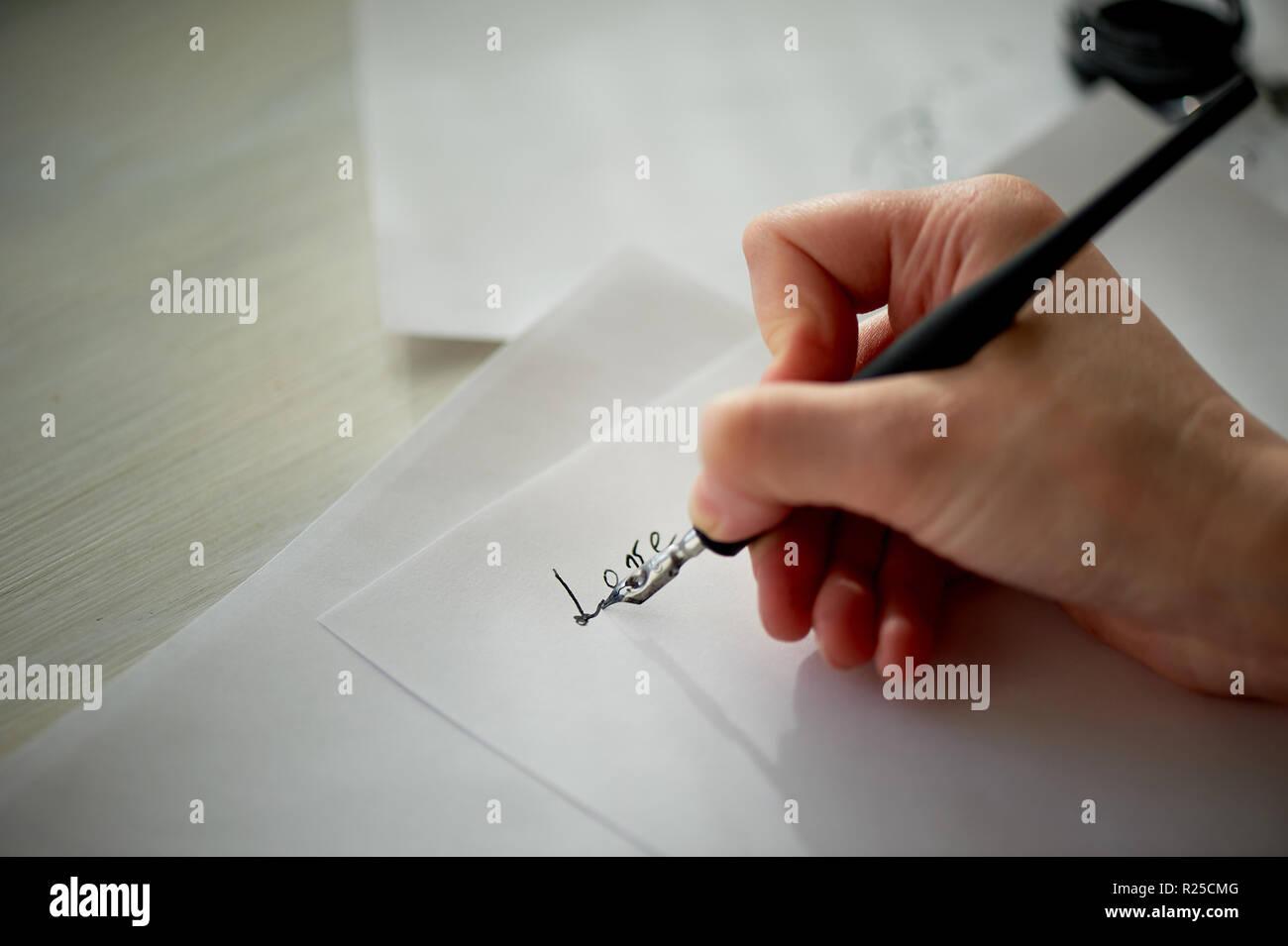 Die Hand einer Frau schreibt mit Tinte, einen Füllfederhalter. Schreiben. Der kreative Prozess der Erstellung einer Arbeit, das Wort Liebe Stockbild