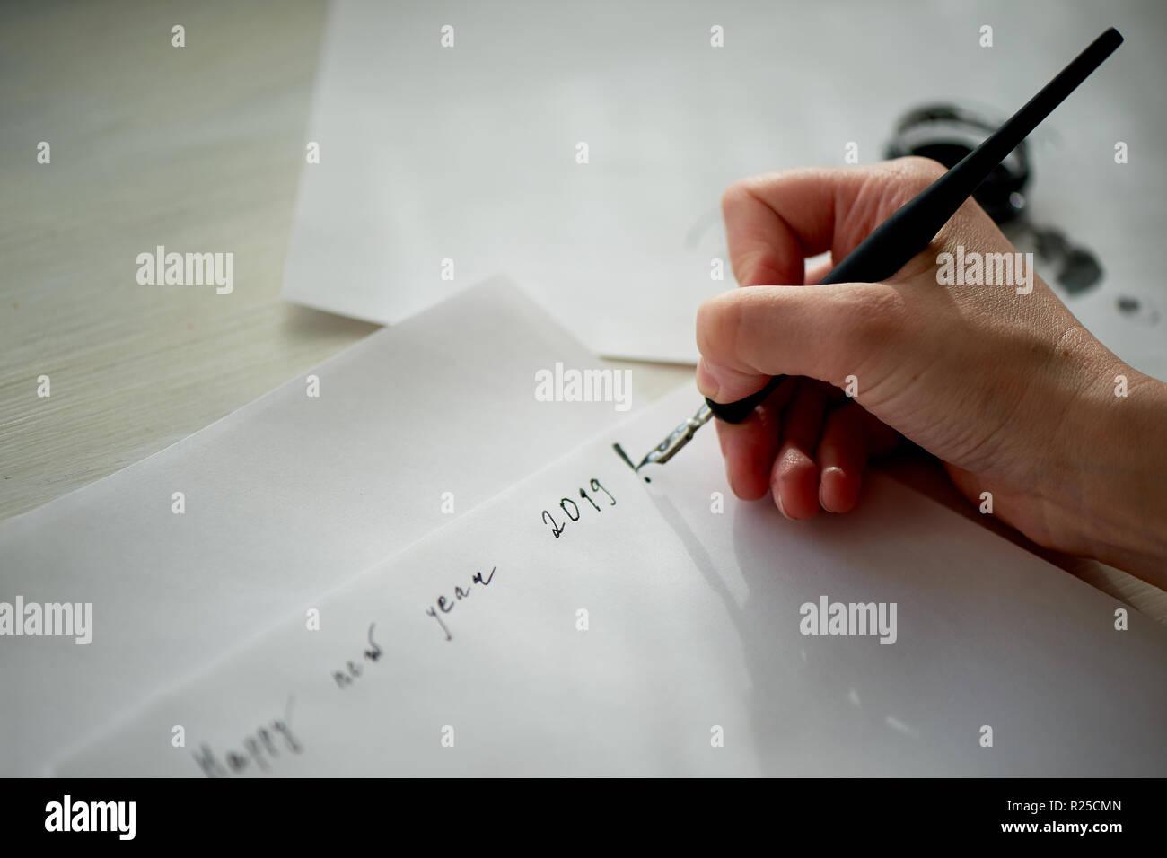 Die Hand einer Frau schreibt mit Tinte, einen Füllfederhalter. Schreiben. Der kreative Prozess der Erstellung einer Arbeit. Phrase neues Jahr 2019. Merkzettel und Pläne Stockbild