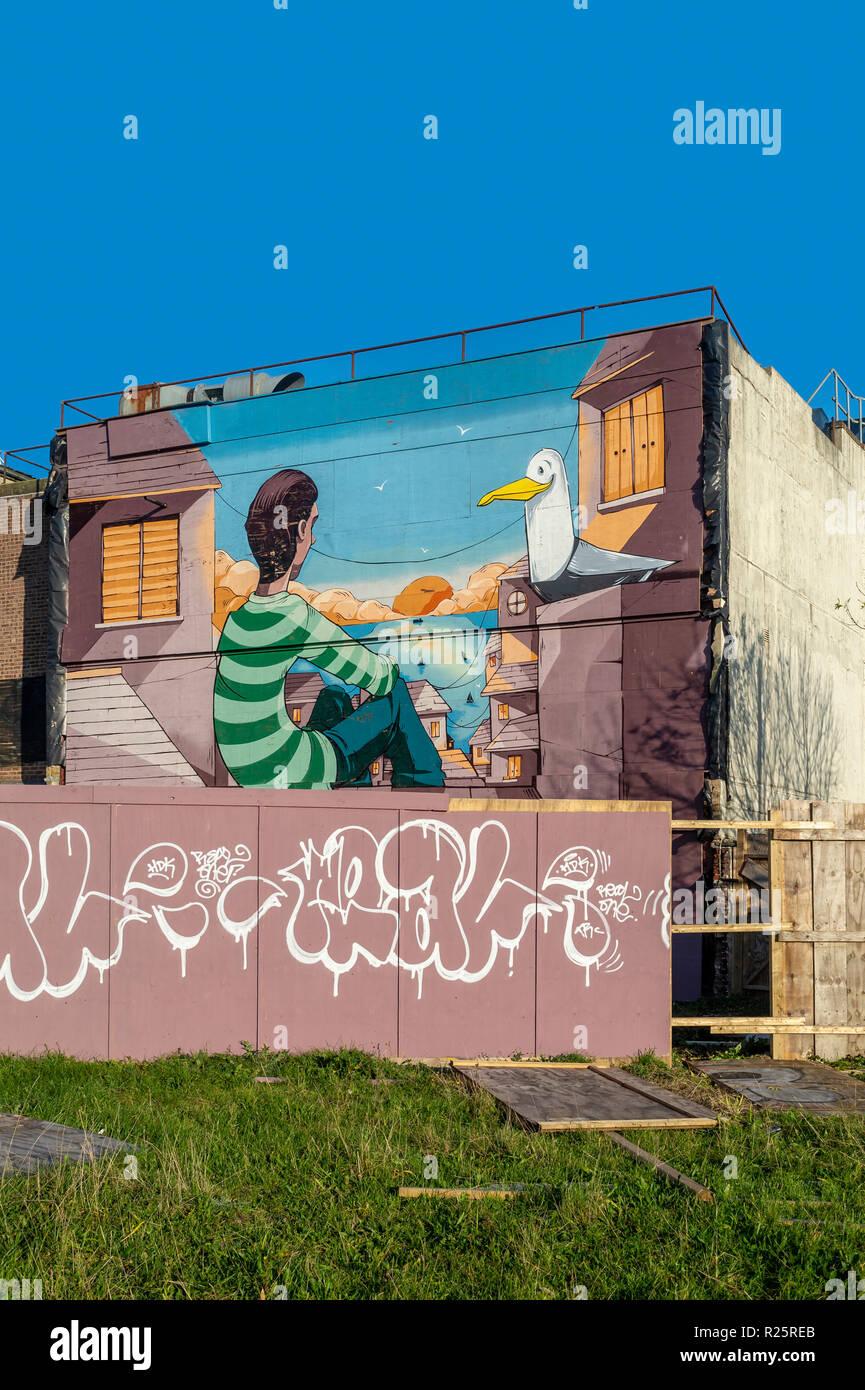 Street Art Wandbild an der Seite eines Gebäudes gemalt, Mann mit einer Möwe mit Meerblick. Stockbild