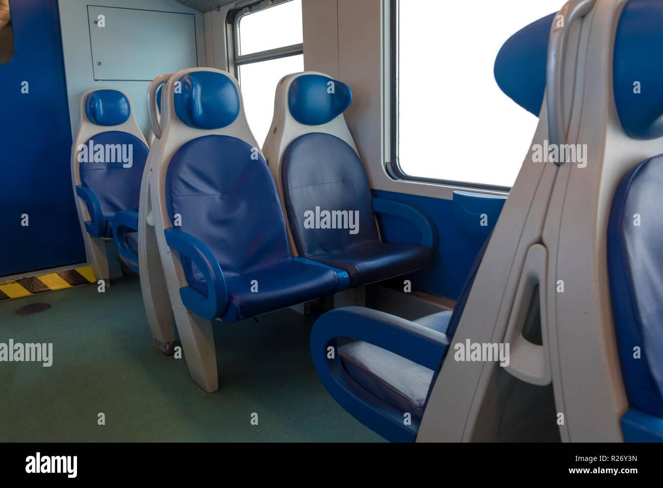 In der Kabine des modernen Express. Niemand in blauen Stühlen am Fenster. Unschärfe. Komfortable Stühle und Tisch im Vordergrund, weißer Hintergrund Stockbild