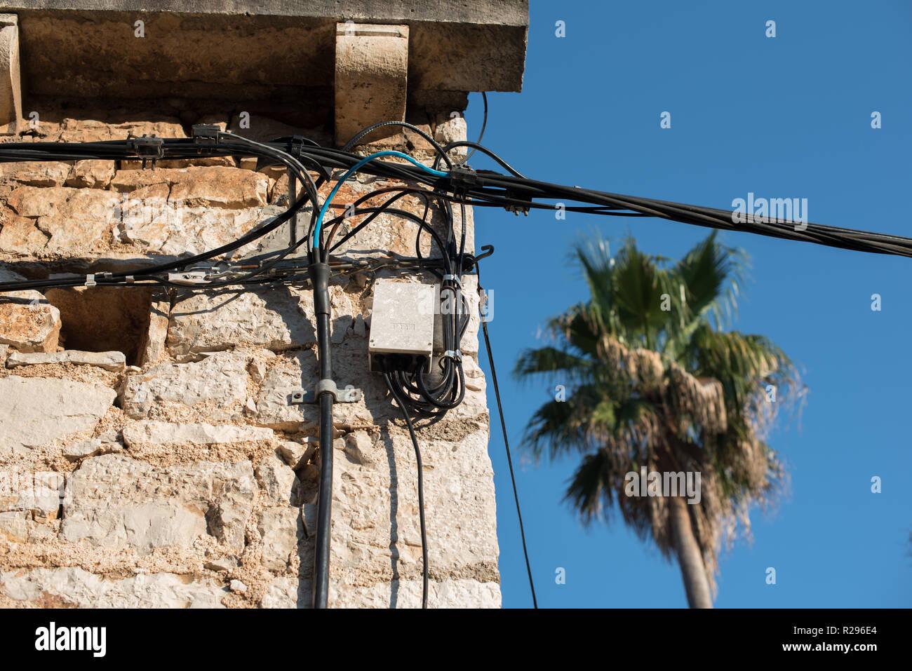 Elektrische Leitungen auf einem alten Haus aus Stein angebracht. Alte Architektur. Stromübertragung. Die Glühbirne auf dem Gebäude. Street Light. Stockbild