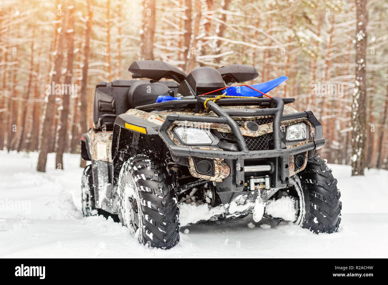 Close-up ATV Allrad Quad Bike im Wald im Winter. 4WD-Fahrzeug terreain stand bei starkem Schneefall mit tiefen Spur. Saisonale extreme Sport Abenteuer und Reise. Copyspace Stockfoto