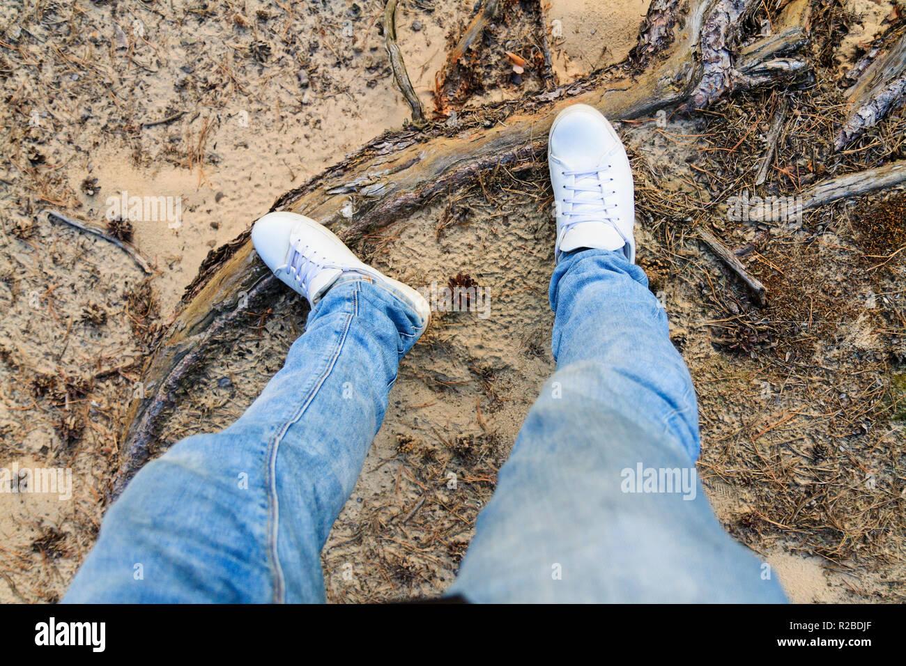 38bd11dca86e Beine in weißen Turnschuhen und Jeans unter Natur Stockfoto, Bild ...
