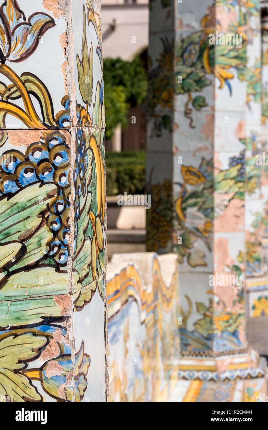 Bunte Fliesen- Säulen und Sitzbank im Garten des Kreuzgangs im Santa Chiara Kloster in der Via Santa Chiara, Neapel, Italien. Stockbild
