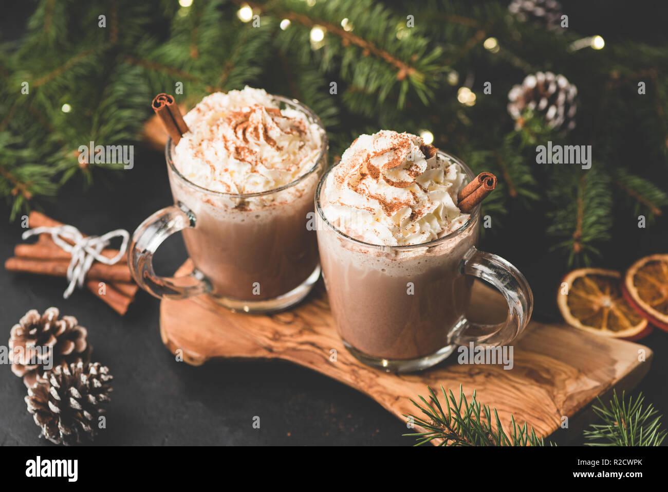 Weihnachtsbeleuchtung Tannenzapfen.Zwei Tassen Heißer Schokolade Mit Schlagsahne Und Zimt Auf Holz Das