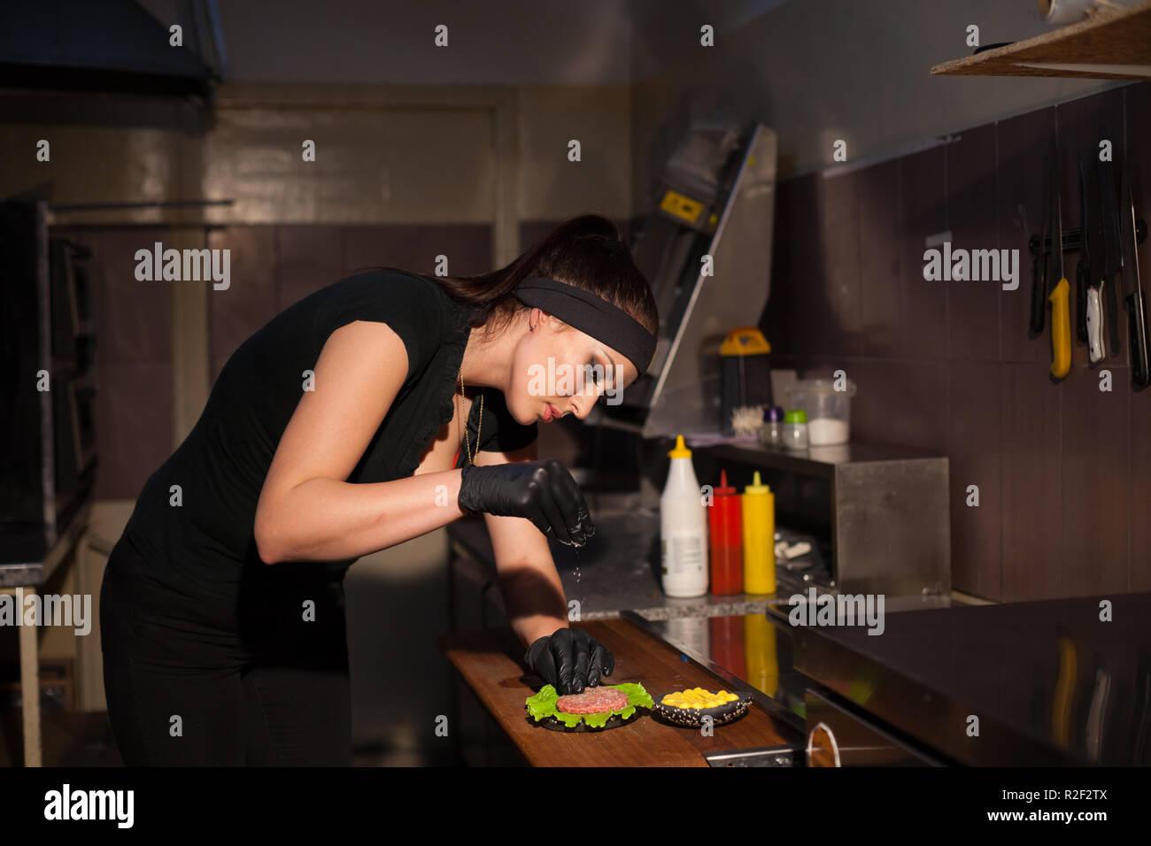 Schöne Frau Küchenchef bereitet einen Hamburger in der Küche des ...