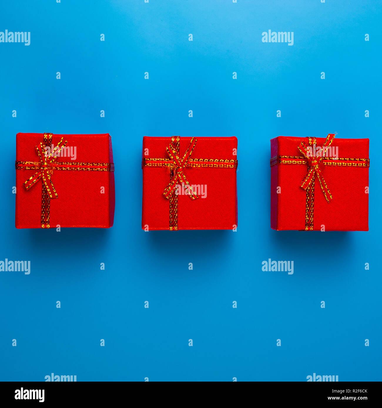 Blog Weihnachtsgeschenke.Drei Rote Boxen Mit Weihnachtsgeschenke Liegen Auf Einem Blauen