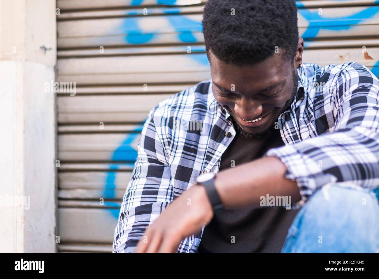 Schöne fröhliche schönen jungen schwarzen afrikanischen amerikanischen lächeln und Spaß beim Sitzen und in der Stadt mit dem städtischen Hintergrund entspannen. jugendlich Konzept für Hipster style Teenager boy Stockbild